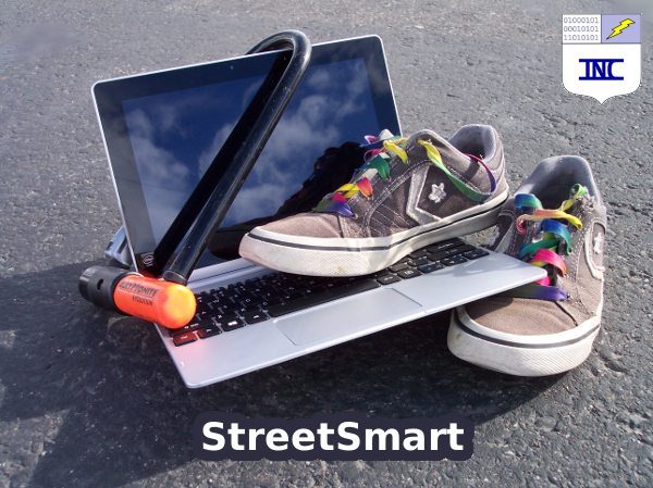 on asphalt: laptop, bicycle lock, and tennis shoes